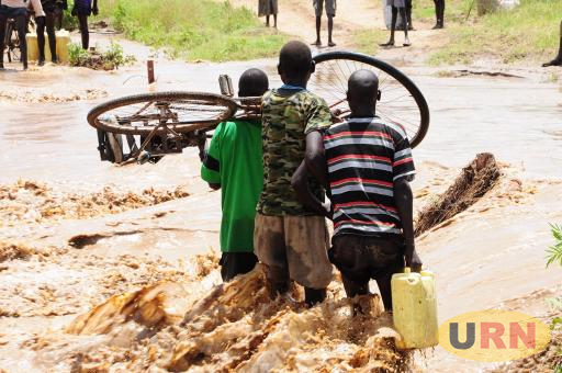 Boys crossing a flooded stream in Karamoja