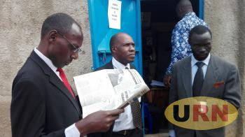 Bruce Twesigye, Vice Chairperson NUEI Makerere University ( reading a newspaper) together with Pastor Michael Eladu the NUEI Kyambogo Chaper Chairperson.