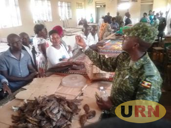 Captain Benon Namanya, Commander of Fisheries Protection Unit, displays immature fish found in Luweero Central Market.