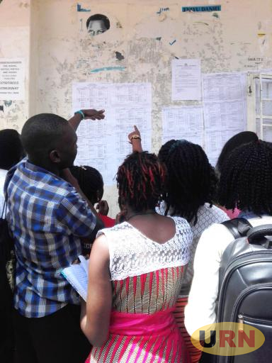 Students at Kyambogo University checking out on the examination time table this afternoon.