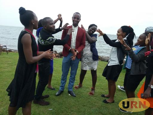 Youth living with HIV and Aids singing for Ismail Harerimana (in maroon jacket) at his birthday party at Nabugabo Sand beach.