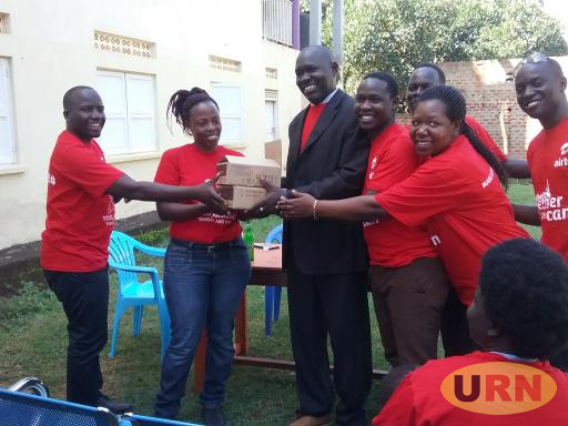 Dr Patrick Olwedo and other healthcare workers in Gulu receiving the donation from Airtel official Mike Kyazze.