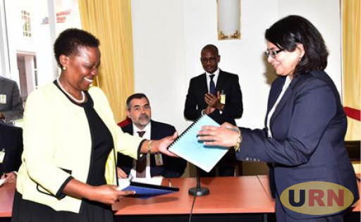 Energy and Mineral's Minister, Engineer Irene Muloni exchnaing papers with Yaatra Ventures Chief Rajakumari Jandhyala at State House Entebbe last week