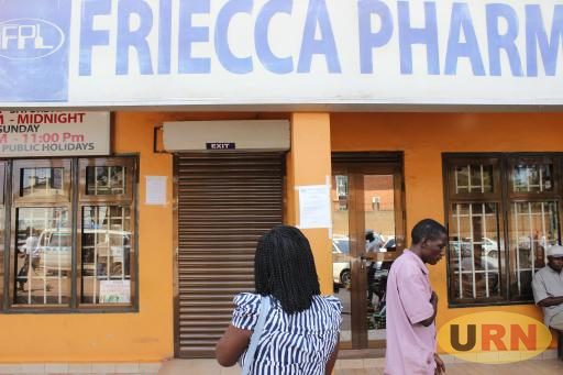 A woman reads a public notice on closed Friecca Pharmacy premises in Wandegeya on Saturday.