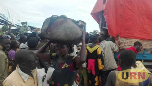 Newly arrived refugees collecting their belongings from a truck in Kyangwali refugee settlement.