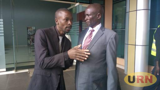 Dr kello in a grey suit together with his lawyer  Semakadde Outside Court in Kampala.