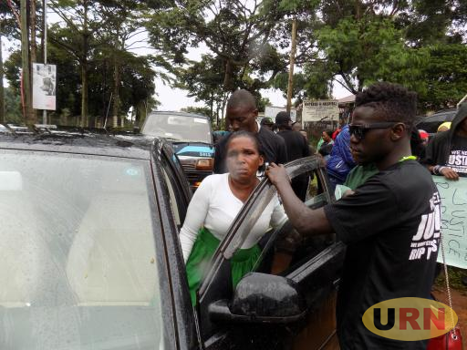 Moses Ssekibogo's mother Jane kasubo being supported to enter a car at Entebbe magistrates court
