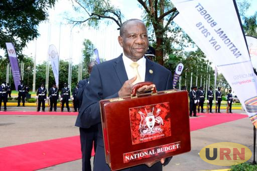 Finance Minister Matia Kasaija displaying the budget for the coming financial year 2018/2019.
