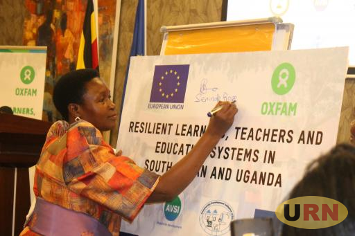 State Minister for Primary Education, Rose Mary Nansubuga Seninde autographing the project poster at Mestil Hotel and Residences in Kampala on Thursday.