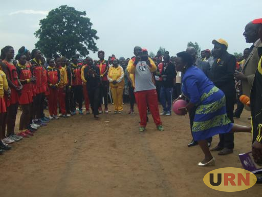 Minister Grace Kwiyucwiny throwing a ball to kick start the She Cranes verses select Team at Barifa stadium