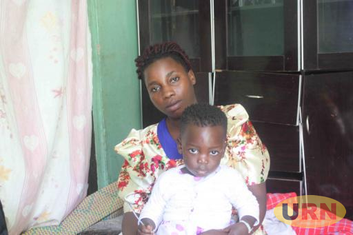 Annet Nansubuga, widow, with their one-year-old daughter