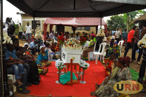 Family members seated around the casket of Resty Nalinya Mbabazi