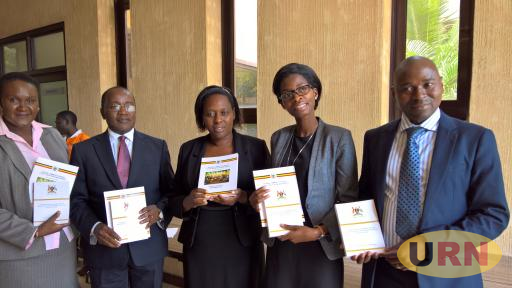 Dr. Musinguzi (2nd) together with Ministry of Health officials show off the consolidated HIV treatment guideline