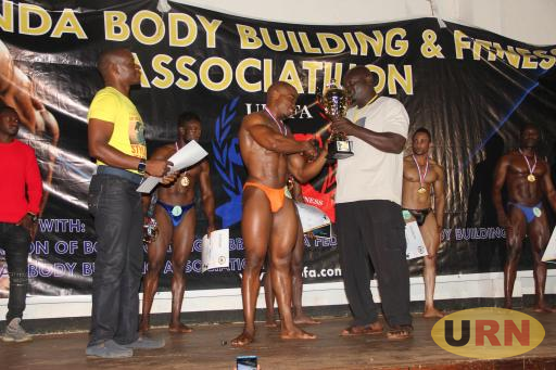 Anatoli Kato recieves a trophy after winning the body building and fitness competitions held at the Jinja municipal town hall on Saturday.