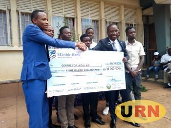 The Acquitted students in the Middle as Lawyer Isaac Ssemakadde Receives a Check of Ugx 8 million for their Legal Fees.