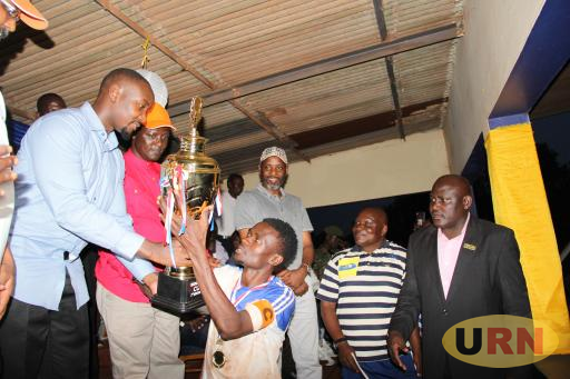The kyabazinga of Busoga, H.R.H William Gabula Nadiope hands over a trophy to the captain of Kigulu chiefdom, Sande Nyandwi.