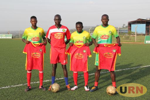 BULFC head coach, Peter Onen (in red) poses for a photograph with the new players.