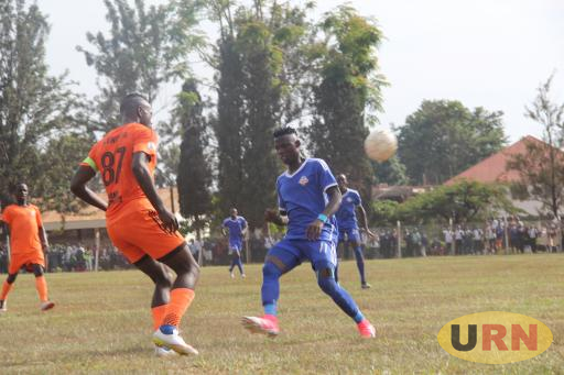 K-Jinja SSS's striker, Joel Madondo dribbles the ball over Tooro united's Mike Kawoya at the mighty arena stadium on Tuesday.