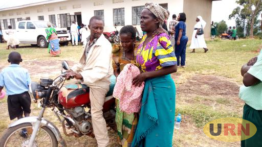 An Elderly Woman being helped from Boda Boda to receive free medical care at Masaka diocese's health camp. Bishop Kaggwa is considering a common home for such people .jpg