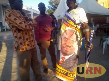 Abdullah Lomongin, the PWD District Councilor in Moroto covering self with Lomonyang's banner.
