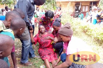 Relatvies help the mother of the deceased Esther Namagembe who collapsed after confirming death of her child