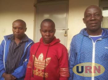 Mubarak Kirunda (in blue hood and t-shirt) and two other suspects at Kisoro police station