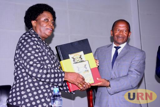 Professor Mary Okwakol, the UNEB Board Chairperson handing over UACE results to John Chrysestom Muyingo, the State Minister for Higher Education.