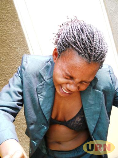 Anita Natukunda,the suspected bank robber shying away from camera after her arrest
