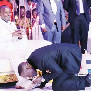 Journalist Joseph Kabuleta kisses ELvis Mbonye feet
